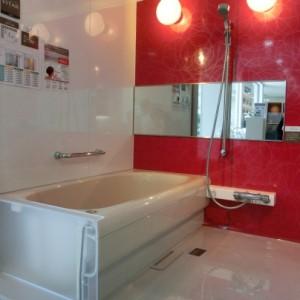 システムバスは白い床と壁に白い浴槽。鏡のある壁だけは真っ赤な壁になっています。