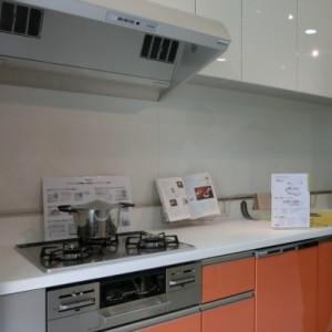 システムキッチンはオレンジの扉、レンジフードがお掃除しやすいタイプです