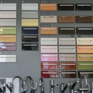 グレーの壁に、扉を小型化したサンプル38枚貼り付けてあります。その手前には台所用シングルレバー水栓金具が8つ横に並んでいます。