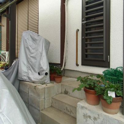 白い壁にダークブランの勝手口のドアギリギリの位置に木製手すりを設置しています。コンクリート製の階段が狭いのです。
