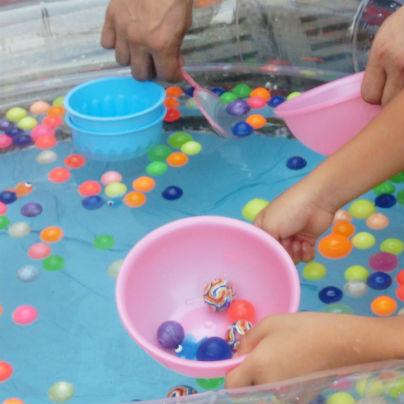 プールにスーパーボールが数十個。ピンクの小さなボウルにお子さんがスーパーボールを5つほど掬っています。