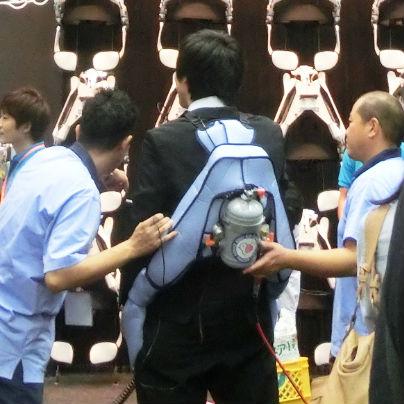 黒いスーツを着た男性が背中に水色のランドセルのようなものを背負っています。