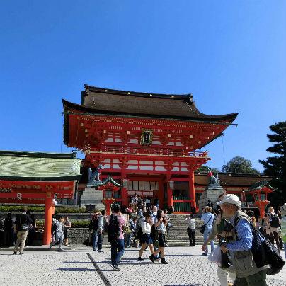 真っ青な空を背景に伏見稲荷大社の朱い楼門、数十人の参拝客が映っています。