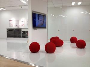 白い床と壁で左側にスケルトンにしたシステムキッチン。中央に大型の液晶モニターで、赤いボール状の椅子が7つ映っています。