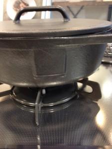 コンロは、黒いガラスの天板に、黒いごとく。そのごとくの上にやはり黒い鋳鉄製の鍋が載っています。
