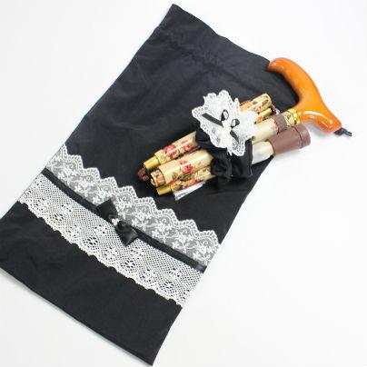 黒い巾着のうえにシュシュで束ねた折りたたみ式杖をおいています。