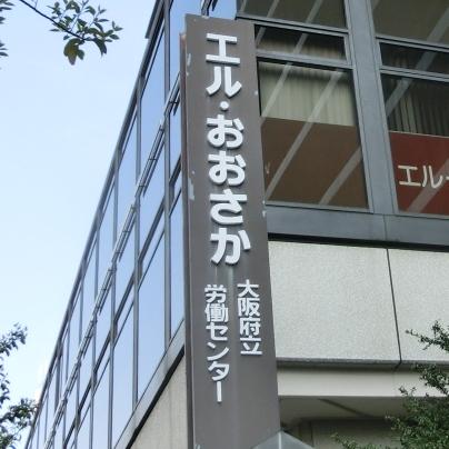 濃い褐色で縦長の看板に白い文字でエル・おおさか 大阪府立労働センターと書いてあります。