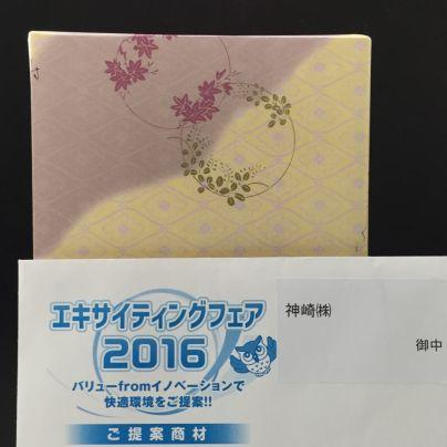 和菓子の包み紙は黄土色と薄紫。その手前にエキサイティングフェア2016と書いた招待状が置いてあります。