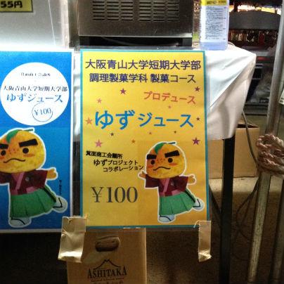 黄色い看板の右には箕面のキャラクター「たきのみちゆずる」その上には水色でゆずジュース、左には黒色で¥100と書いてあります。