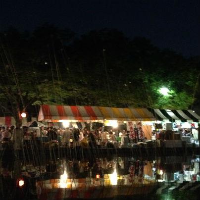 池の向こうには夜店のテントで、その下は明かりがいくつか。多くの人で賑わっています。