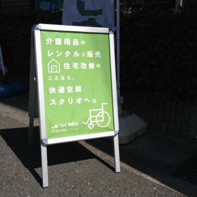 銀色のアルミフレームに緑の背景、白い文字で「介護用品のレンタルと販売 住宅改修のことなら快適空間スクリオへ。」と書いてあります。
