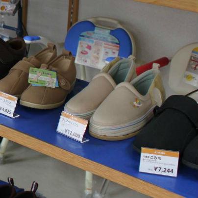 青い棚に、ベージュの介護靴が二足、黒の介護靴が一足おいてあります。