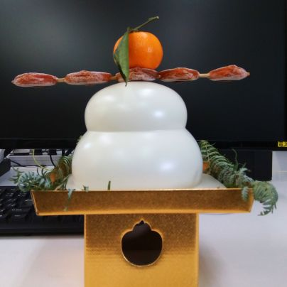 金色の三方の上に鏡餅と橙、干し柿が載っています。