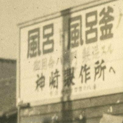 古い写真には看板が写っていて「風呂・風呂釜 神崎製作所へ」