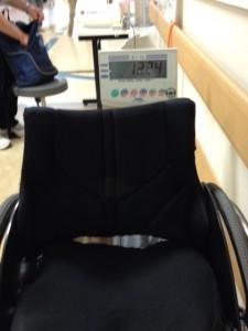 車いすごと計れる体重計で、車いすだけの重量を計っています。