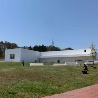 芝生の上に白くて四角い横長の建物が建っています。窓はほとんどありません。