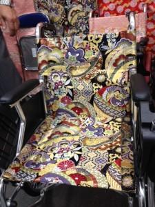 車いすを右斜め前から撮影していて、背もたれシートと座面シートが肌色に牡丹模様の西陣織りになっています
