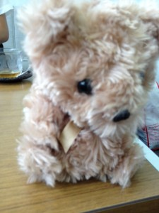 机の上に置いたしゃべる犬のぬいぐるみを左前から撮った写真。