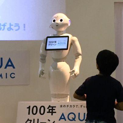 白い壁とスクリーンを背景に白いヒト形ロボットペッパーが子供を前に説明をしています。