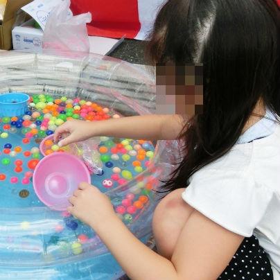 子供用のプールにたくさんのスーパーボールを浮かべ、女の子がピンクのボウルをもって掬っています。
