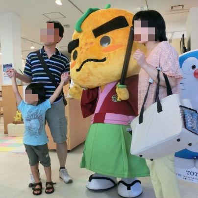 滝ノ道ゆずるを中心に左に若いお母さん、右に若いお父さん、お父さんのまえに小学校一年生くらいの男の子がカメラのレンズに向かっています。