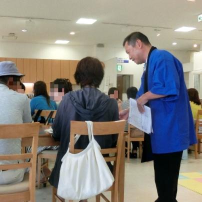 椅子に腰掛けたご夫婦に青い発布をきた男が御礼に話しかけています。