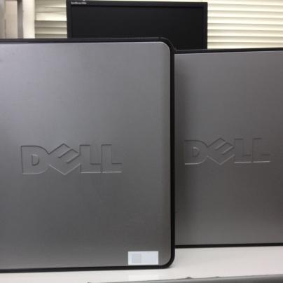 古い銀色のパソコンが2台、横向きになり前後に並んでいます。