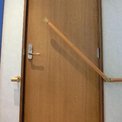 扉を横切る遮断機手すりが斜めに上がっている様子。