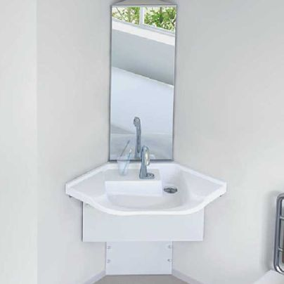 白い壁のお部屋のカドに白い手洗い器、その上に細長い鏡が設置してあります
