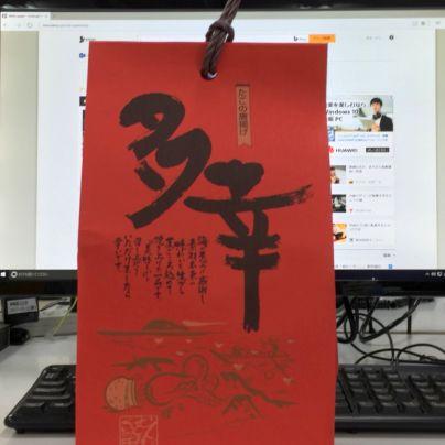 パソコンのモニターの前に赤いパッケージに墨色の毛筆で多幸の文字