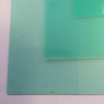 白い机の上には緑で半透明の保護シートが3枚載っています。
