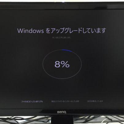 黒い背景のパソコンモニター、Windowsをアップデートしています。8%と画面に出ています。