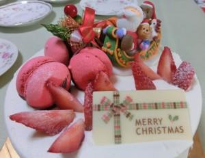白いケーキの上に、赤いイチゴと赤いマカロン、そしてクリスマスケーキにはMerry Christmasと書いたチョコレートが載っています