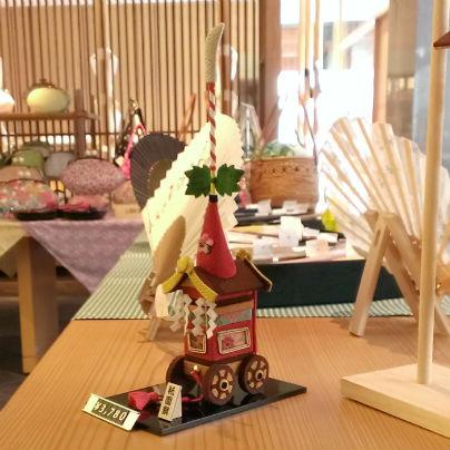 木製の机の上に長刀鉾のミニチュアが置いてあります。