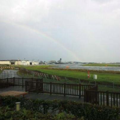大阪国際空港で滑走路の向こうには曇り空、円弧の右半分で虹が架かっています。
