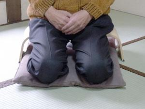 アグラスツールの上にズボンをはいたひとが座っています。