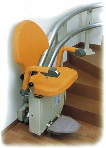 階段昇降機・いす式・自由生活・曲線階段用は曲線階段なので右に大きく回るレールとオレンジ色の座椅子です。