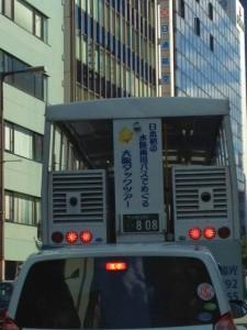 軽自動車の屋根の上にストップランプが見える水陸両用バスが映っています。