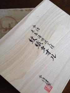 白い桐箱の横は約40センチ、縦は約30センチに墨の毛筆で「今治  来島海峡波状文様 紋織タオル」と書いてあります。
