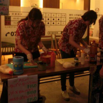 アロハシャツを着た二人の若い女性が、長机の上でソーセージを調理しています。