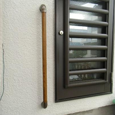 白い壁にダークブラウンの勝手口のドア、その左側でドアの下ギリギリに木製の縦棒手すりを設置してあります。