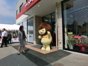 クリナップ北大阪ショールームの外、入り口の真ん前に立つ頭が栗の形をした黄色い猫のような着ぐるみが立っています。