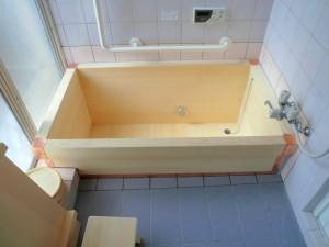 白いタイル貼りの浴室に、白い木風呂が据え付けられます。