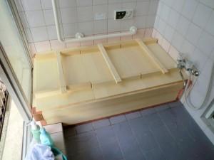 タイル貼りの浴室に据え付けている木風呂に、風呂ふたを閉めています。