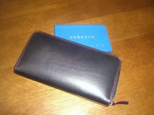 新しい財布に大阪府の身障者手帳を入れようとしている様子