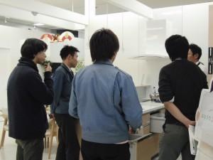 キッチンを前にしてしてノーリツの営業担当者さんから説明を聞く当社々員です