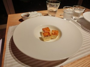 白い大きなお皿の真ん中に小さな黄色い立方体のカタリーノが3つ乗っています