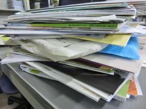 事務机のうえに福祉機器の資料が何十冊も平積みになっています。
