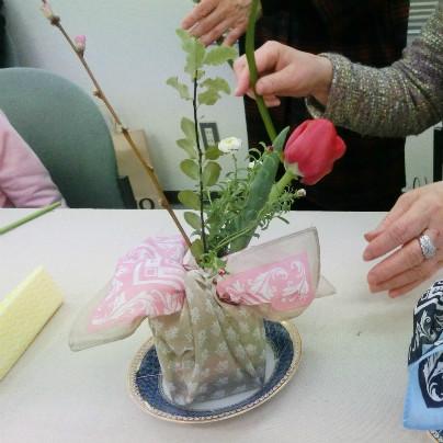 白い机の上に赤い花をつけたフラワーアレンジメントが置いてあります。