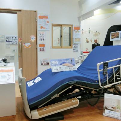 手前には介護ベッド、背もたれを起こしています。その向こうには木製扉、扉の向こうはトイレです。